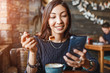 woman surfing in wi-fi mobile internet, while sitting in cafe with cup of coffee and cake