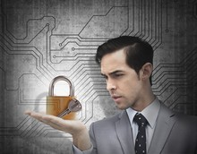 Concentrated Businessman Holding A Padlock