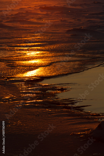 Staande foto Rood paars flares of the sun on the ice on the river