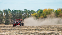 Quad Bike In Thick Dust Rides On Plowed Field