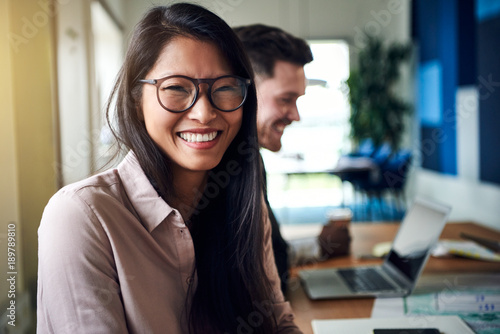 Fototapeta  Smiling young Asian businesswoman sitting with colleagues in an office