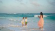Little adorable girls and young mother at tropical beach in warm evening. Mom take a photo of beautiful kids on the sunset