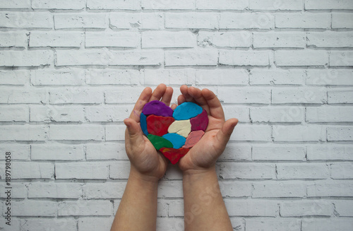Fotografia  Child's hands holding a multicolored heart on white background with place for your text