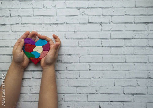Fotografía  Child's hands holding a multicolored heart on white background with text space