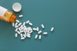 Leinwandbild Motiv White Pills on a Teal Background