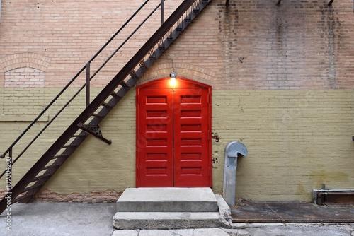 Red wooden door entrance, overhead light, stairway, brick wall, copy space