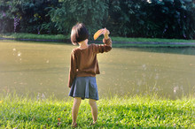 Asian Little Girl Throw A Leaf To The Lake While Admires The Nature.