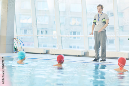 Young Instructor Standing By Edge Of Swimming Pool And Gicing