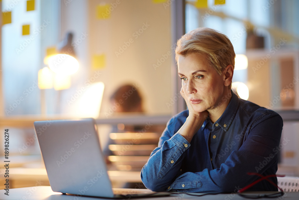 Fototapeta Mature professional watching online conference or webinar in laptop while sitting in office