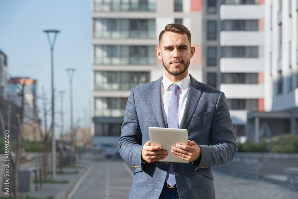 Fototapeta Businessman or real estate agent with tablet computer against new building