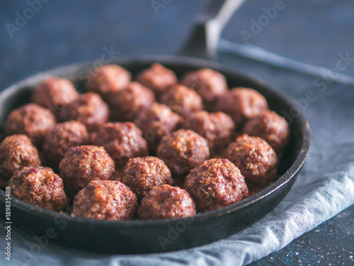 Fotografia Homemade roasted beef meatballs in cast-iron skillet on dark blue background