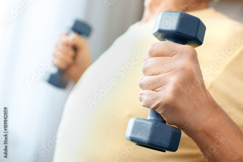 Senior man exercise at home health care with dumbbells body close-up ...