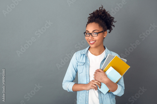 Slika na platnu Young african woman isolated on grey wall studio casual daily lifestyle student