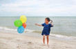 Happy little girl playing colorful balloons on the beach during summer vacation.