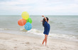 Kid girl running on beach with colorful balloons.