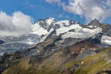 Hiking in Cogne valley, Aosta, Italy. View of Gran Paradiso Group with the namesake summit and Herbetet summit on the right.  Photo taken from TsaPlana, a place outside the park boundaries.