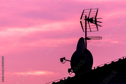 In de dag Candy roze Silhouette of roof with satellite and antenna on nice vibrant violet and pink sky