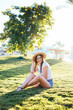 Beauty brunette woman in sunglasses and hat sitting on the grass in sunglasses on summer days
