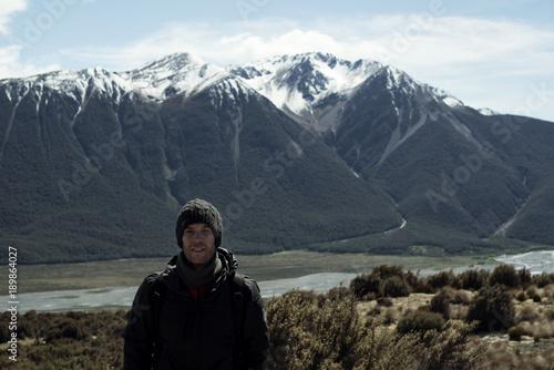 Photo Hombre joven posando frente a un paisaje de montaña en la naturaleza