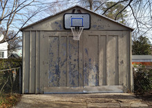 Basketball Hoop Attached To Weathered Residential Neighborhood Garage.