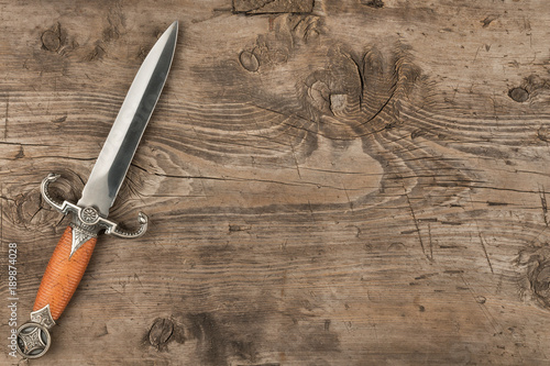 Fotografía Knife, dagger on a wooden surface, with a place for your text.