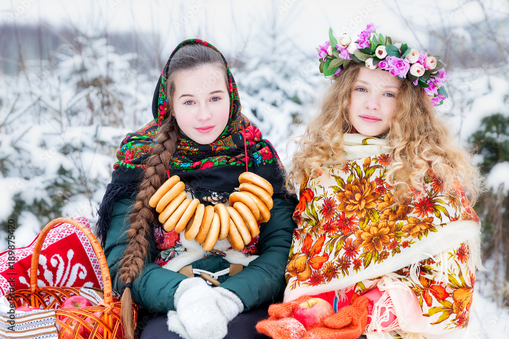 Fototapeta Girls in Russian national clothes in the winter landscape