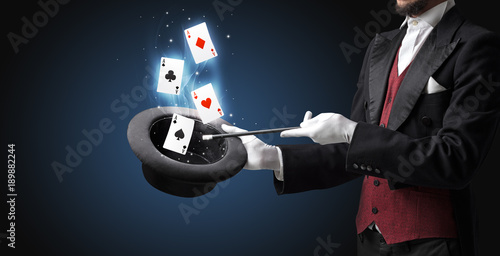Photographie Magician making trick with wand and playing cards