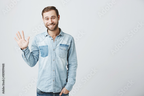 Fototapeta Friendly positive smiling young Caucasian man with stubble and dark hair in trendy denim clothes waving with hand, hailing friends while having fun indoors