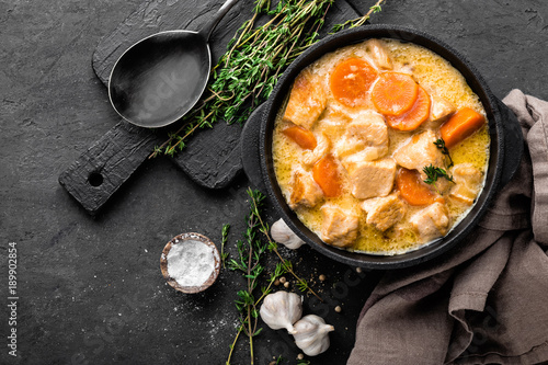Meat stew, chicken fillet in sauce with carrot in a cast iron pot, top view