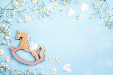 Blue Background With Mini Rocking Horse Toy And Gypsophila Flowers. Copy Space.
