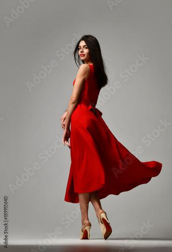 Pretty brunette woman in formal red dress stiletto heels shoes Fototapeta
