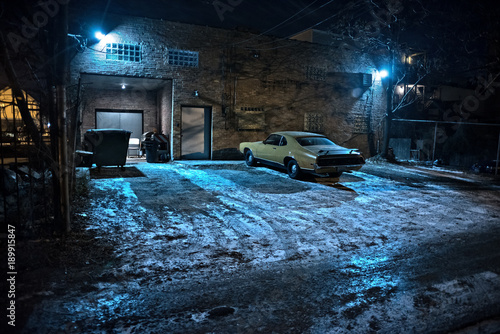 Fotografie, Obraz  Vintage muscle car in a dark Chicago city urban alley on a winter night