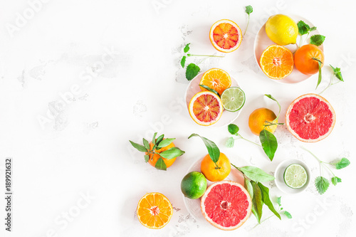 Foto op Aluminium Vruchten Fruit background. Colorful fresh fruits on white table. Orange, tangerine, lime, lemon, grapefruit. Flat lay, top view, copy space