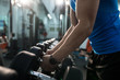 Side view close up of strong male hands picking up dumbbells from equipment stand in modern gym, copy space