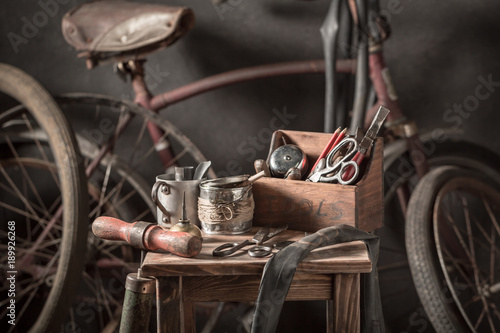 Vintage bicycle repair workshop with tools, wheels and tube