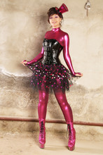Beautiful Woman Stands In A Crimson Fetish Overalls, Black Shiny Bdsm Corset With Buckles, Burlesque Tutu Skirt And Cute Pinup Hat With A Veil