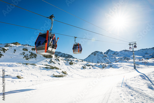 Fotobehang Gondolas ski lift gondolas against blue sky over slope at ski resort on sunny winter day at Italy Alps
