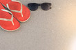 Sunglasses with sandals on beach for relax time.