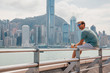Hong Kong, China. August 30, 2017. Young man sitting on the coastline in Hong Kong watching city skyline panorama from across Victoria Harbor drinking juice.