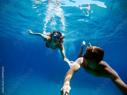 Underwater selfie with a stick of young excited happy love student couple swimming and enjoying with goggles in the exotic turquoise sea at summer vacation.