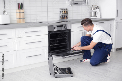 Young man repairing oven in kitchen Canvas Print