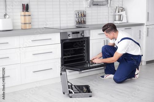 Fotografía  Young man repairing oven in kitchen