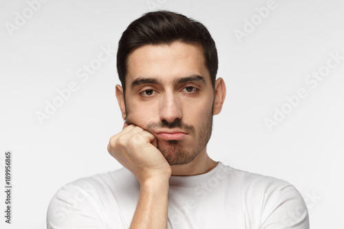 Foto  Close up portrait of bored young man in white tshirt with head on chin isolated
