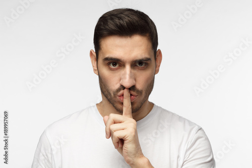 Photo  Close up shot of handsome strict man with shh gesture, asking for silence or to