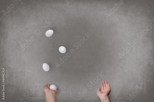 Female hands juggle white eggs. Food Concept