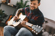 Young guitarist hipster at home with guitar sitting playing inspired