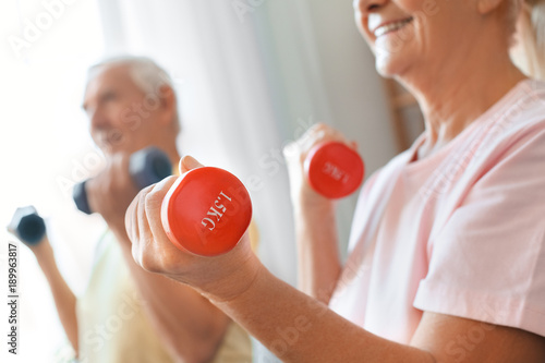 Senior couple exercise together at home health care dumbbells close ...