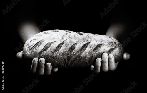 Door stickers Bread A loaf of freshly baked bread in the hands of a baker on a black background.