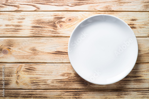 White plate on wooden Kitchen table.