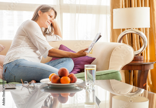Woman on the couch with a magazine Poster